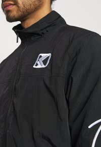 Karl Kani - SIGNATURE TRACKJACKET UNISEX - Summer jacket - black - 4