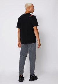Calvin Klein Jeans - RELAXED BADGE TEE UNISEX - Print T-shirt - black - 2