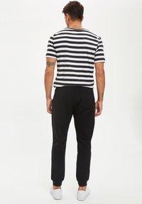 DeFacto - Pantalones deportivos - black - 2