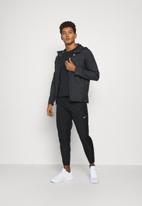 Nike Performance - ESSENTIAL PANT - Pantalones deportivos - black/reflective silver - 1