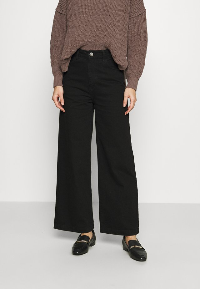 CALM - Flared jeans - black