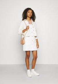 Tommy Jeans - SHORT DUNGAREE SNAP DRESS - Denim dress - work white rigid - 1