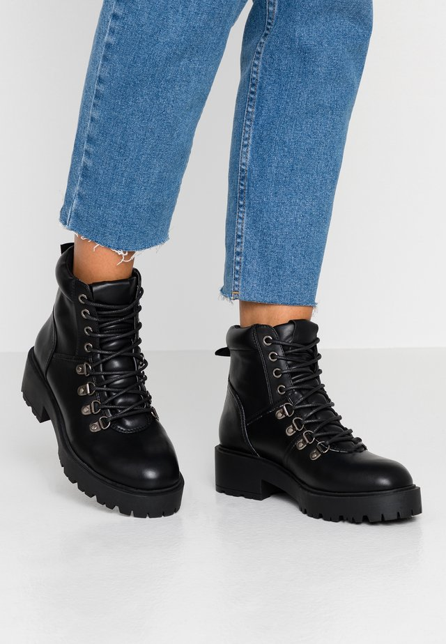 PRIYAA - Platform ankle boots - black