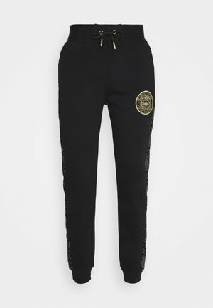 DINAS - Tracksuit bottoms - black
