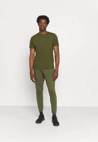 Nike Performance - TEE CREW SOLID - Basic T-shirt - rough green/black - 1