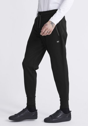 COLLECTIVE  - Tracksuit bottoms - black