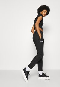 Ellesse - ADALINA - Tracksuit bottoms - black - 4