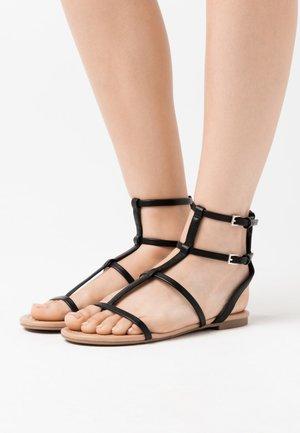 COLISIUMM - Sandalias de dedo - black