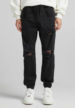 MIT ZIERRISSEN - Jeans Tapered Fit - black