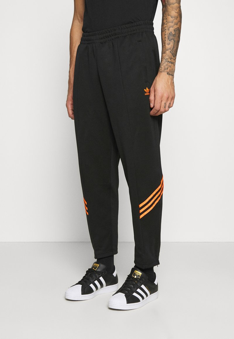 adidas Originals - TRACK PANT UNISEX - Tracksuit bottoms - black/trace orange