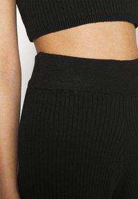 NA-KD - NA-KD X ZALANDO EXCLUSIVE SOFT RIBBED PANTS - Trousers - black - 4