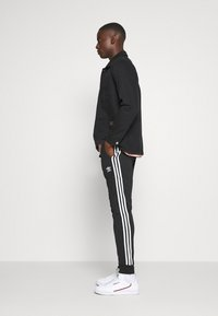 adidas Originals - UNISEX - Pantalon de survêtement - black/white - 4