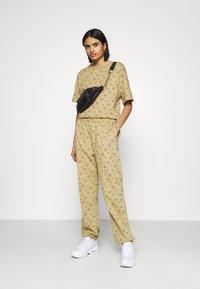Nike Sportswear - W NSW PANT BB AOP PRNT PACK - Tracksuit bottoms - parachute beige - 1