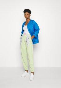 NEW girl ORDER - METALLIC TRIBAL FLAME JOGGERS - Pantalones deportivos - green - 1