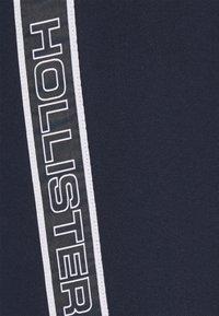 Hollister Co. - LOGO TAPE JOGGER - Tracksuit bottoms - navy - 5