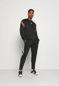 adidas Originals - SWAROVSKI TRACK UNISEX - Sportovní bunda - black/trace orange - 1