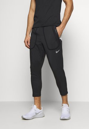 WILD RUN - Tracksuit bottoms - black/white