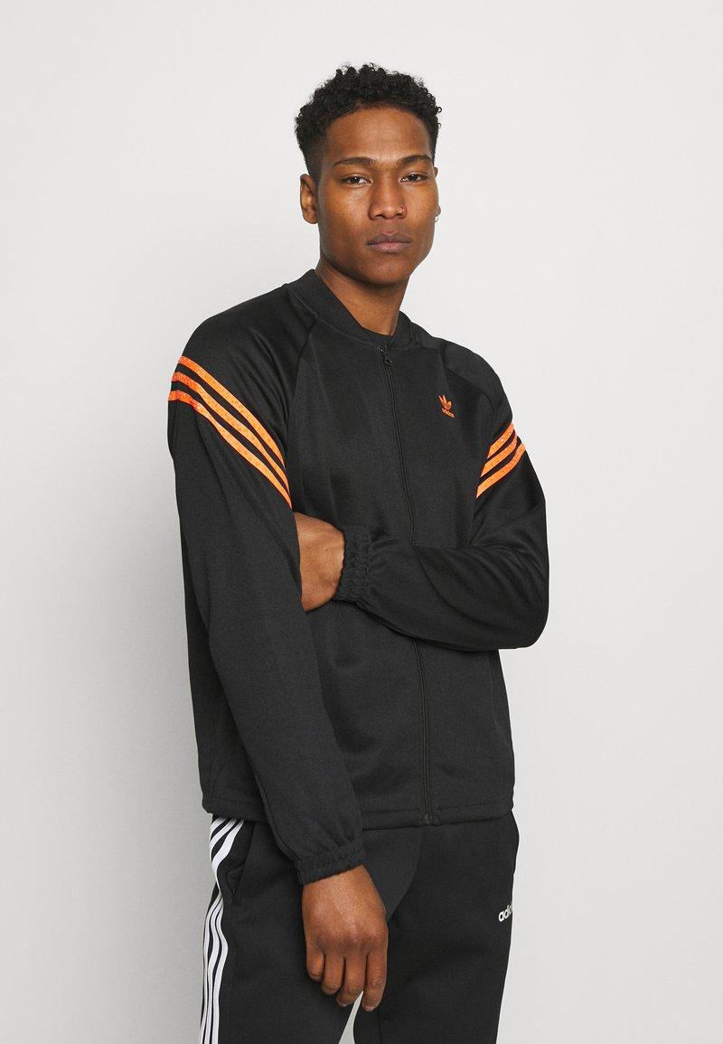 adidas Originals - SWAROVSKI TRACK UNISEX - Sportovní bunda - black/trace orange