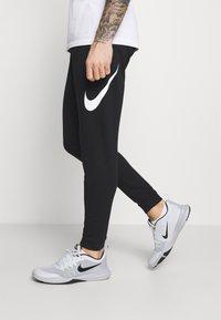 Nike Performance - TAPER - Tracksuit bottoms - black/white - 3