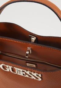 Guess - UPTOWN CHIC TURNLOCK SATCHEL - Handbag - cognac - 4