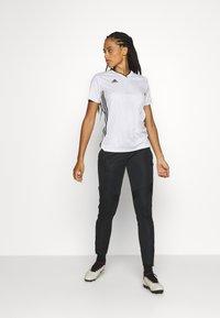 adidas Performance - TIRO - Tracksuit bottoms - black - 1