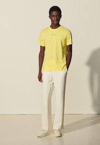 sandro - SOLID TEE UNISEX - Basic T-shirt - jaune citron - 0