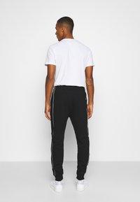 Calvin Klein - TWO TONE LOGO PANT - Tracksuit bottoms - black - 2