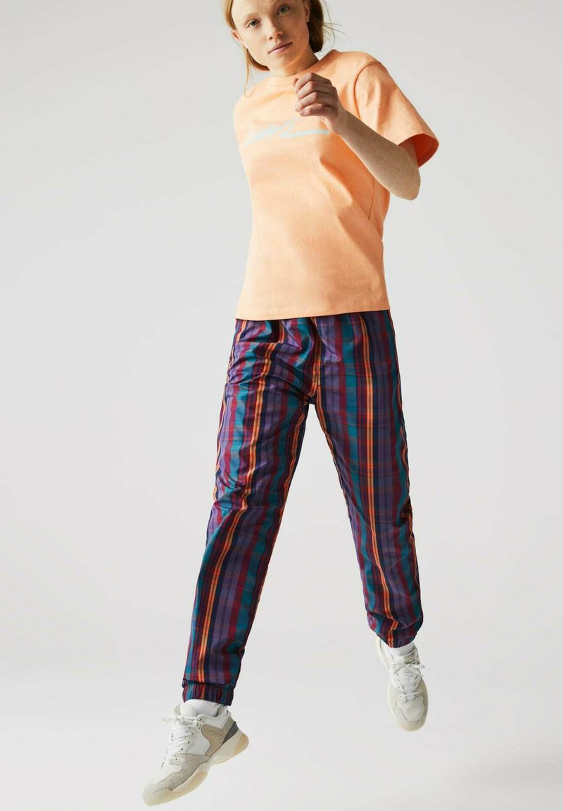 Lacoste LIVE - Tracksuit bottoms - lila / weiß