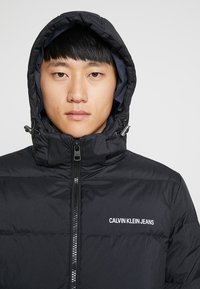 Calvin Klein Jeans - HOODED DOWN PUFFER  - Winter jacket - black - 9