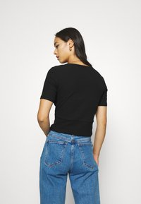 Monki - SISSELA - T-shirts - black dark