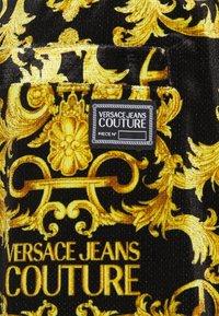 Versace Jeans Couture - TECNO  PRINT LOGO BAROQU  - Tracksuit bottoms - black - 6