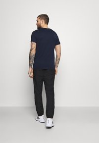 Lacoste Sport - TENNIS PANT TAPERED - Träningsbyxor - black/white - 2