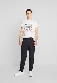 New Balance - ATHLETICS PANT - Trousers - black - 1