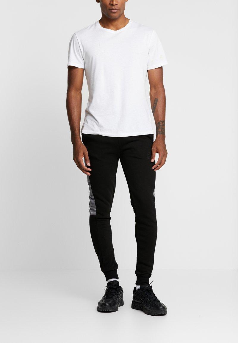 CLOSURE London - CONTRAST CHECKE - Teplákové kalhoty - black