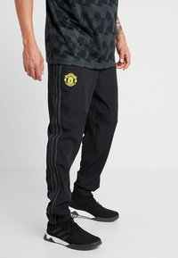 adidas Performance - MANCHESTER UNITED FC - Tracksuit bottoms - black/green - 0