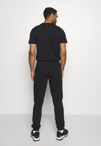 Puma - NU TILITY PANTS - Tracksuit bottoms - black