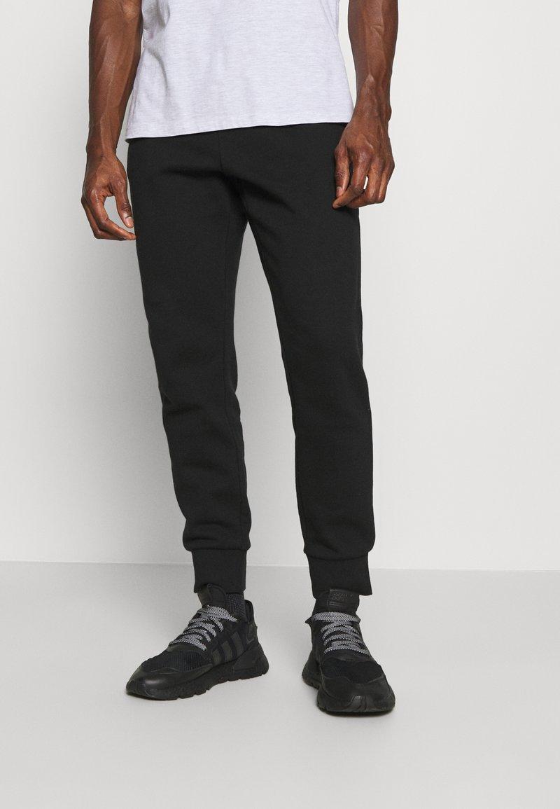 Lacoste - Tracksuit bottoms - black
