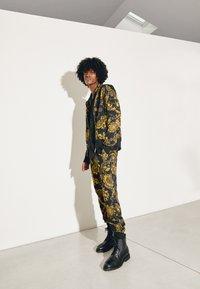 Versace Jeans Couture - PRINT REGALIA BAROQUE - Tracksuit bottoms - nero/oro - 2