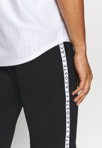 Lacoste Sport - PANT TAPERED - Tracksuit bottoms - black - 6
