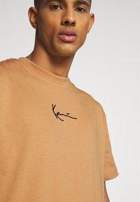 Karl Kani - SMALL SIGNATURE TEE UNISEX - Print T-shirt - beige - 5