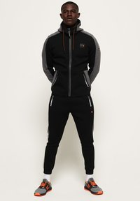 Superdry - MIT FARBBLOCK-DESIGN - Tracksuit bottoms - black - 1