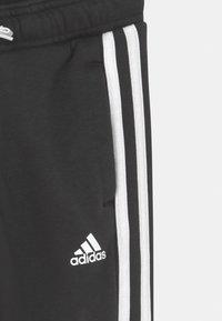 adidas Performance - UNISEX - Tracksuit bottoms - black/white - 2