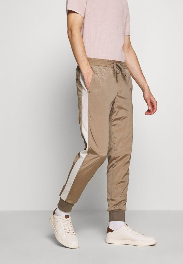 RANDY  - Tracksuit bottoms - beige stone