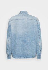 Tommy Jeans - WORKER SHIRT JACKET UNISEX - Denim jacket - light blue denim - 1