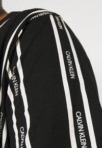 Calvin Klein - VERTICAL LOGO STRIPE - T-shirt med print - black - 3