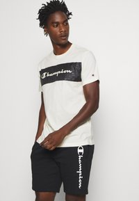 Champion - LEGACY HERITAGE TECH SHORT SLEEVE - T-shirt imprimé - offwhite/black - 0