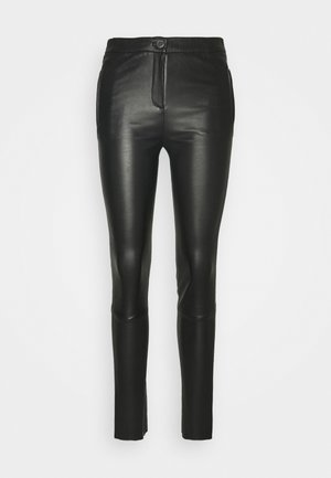 CELESTE - Leather trousers - black
