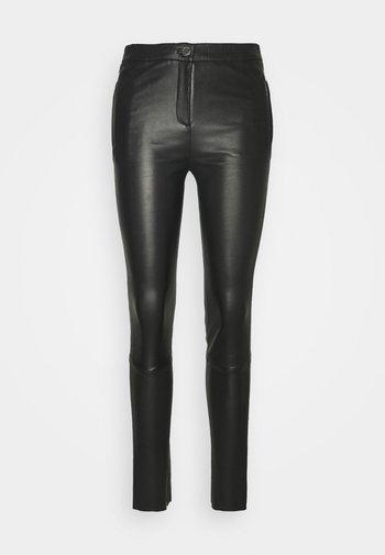 CELESTE - Leather trousers - black