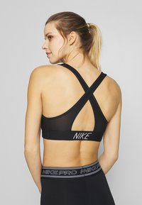 Nike Performance - BRA PAD - Medium support sports bra - black/white