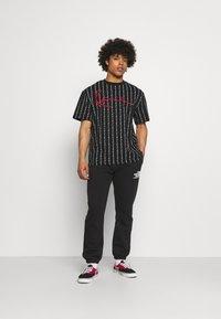 Karl Kani - SIGNATURE LOGO PINSTRIPE TEE - T-shirt z nadrukiem - black - 1